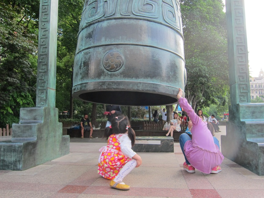 Girls inspecting the old bell